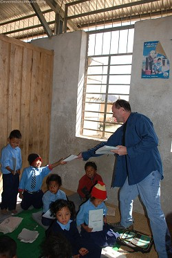 Mike handing out pencils to Nursery students