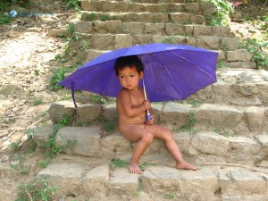 50. Innocent cute child in village under umbrella shadow