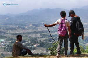 2. Two Students look at something while one sits and admires the view during a break in the hike.